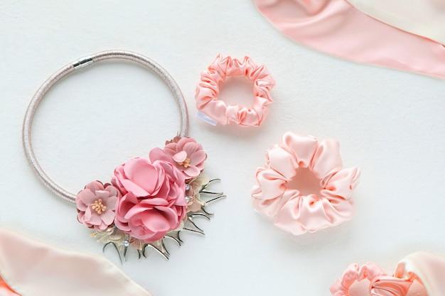 Accessoires pour cheveux roses avec roses. chouchou rose en soie isolé sur fond blanc. outils et accessoires de coiffure à plat comme chouchous colorés, bandeaux élastiques, bandeau à cheveux bobble scrunchie
