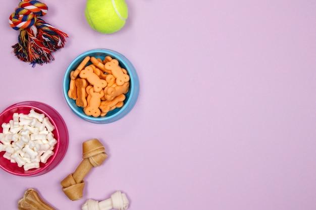 Accessoires pour chiens, nourriture et jouet sur fond violet. plat poser. vue de dessus