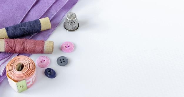 Accessoires pour la couture : bobines de fils, boutons, dé à coudre et centimètre sur fond blanc. espace de copie.