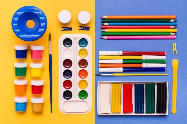Accessoires pour crayons à la créativité, marqueurs, aquarelles, gouaches, pinceaux et pâte à modeler sur fond jaune