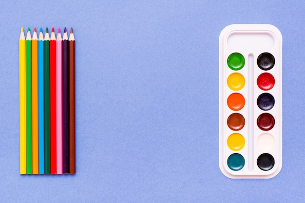 Accessoires pour dessiner des crayons de couleur et des crayons de couleur bleu aquarelle concept contre des aquarelles