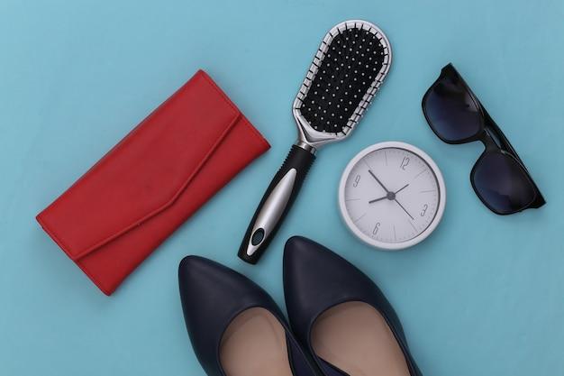 Accessoires pour femmes. chaussures à talons hauts, portefeuille, peigne, lunettes de soleil et horloge sur bleu.
