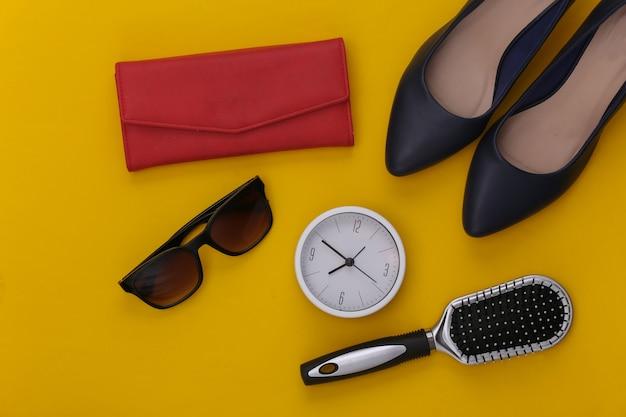 Accessoires pour femmes. chaussures à talons hauts, portefeuille, peigne, lunettes de soleil et horloge sur jaune.