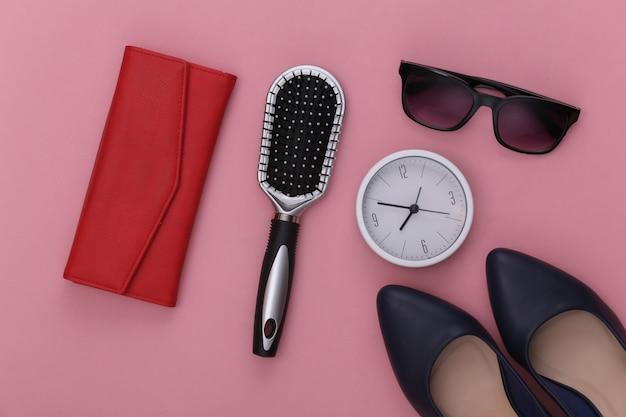 Accessoires pour femmes. chaussures à talons hauts, portefeuille, peigne, lunettes de soleil et horloge sur rose.