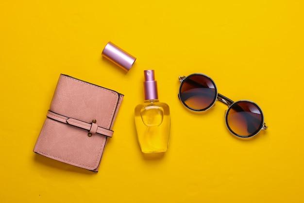 Accessoires pour femmes sur jaune. lunettes de soleil rondes à la mode et bouteille de parfum, portefeuille sur jaune