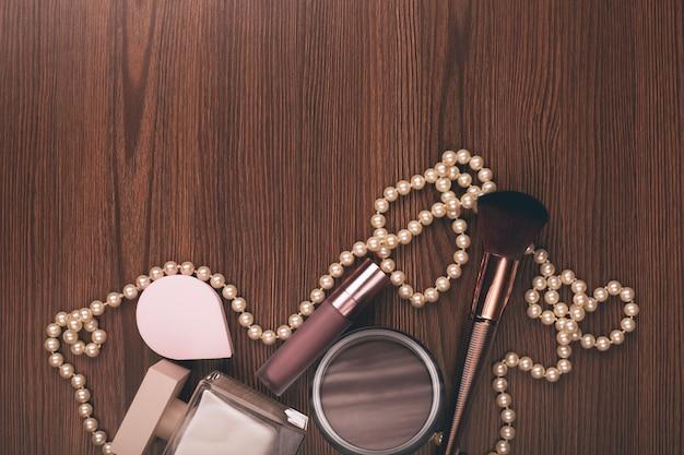 Accessoires pour femmes. pinceau de parfum, de crème et de maquillage sur fond de bois