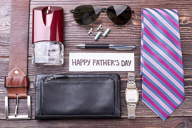 Accessoires pour hommes sur fond de bois. carte de voeux et ceinture. le look élégant vous rend confiant.