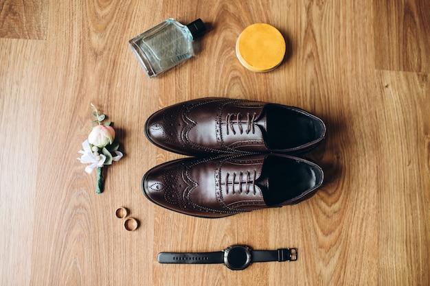 Accessoires pour hommes, parfum, boutonnière, bagues en or, montres et chaussures en cuir du marié sur un plancher en bois.