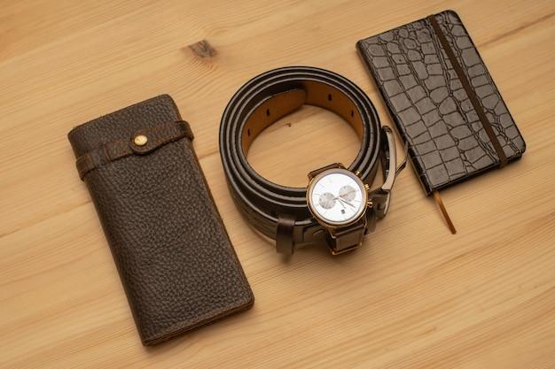 Accessoires pour hommes avec portefeuille en cuir marron, ceinture, carnet et montre sur une surface en bois