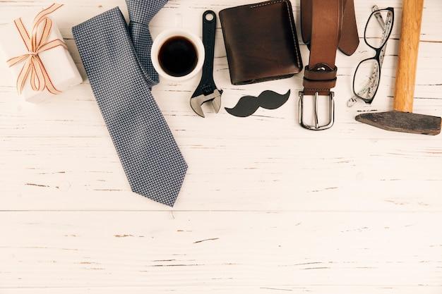 Accessoires pour hommes près de cadeau et tasse de boisson