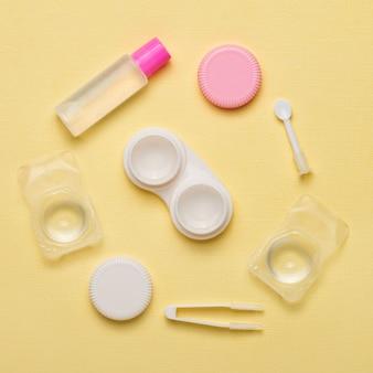 Accessoires pour lentilles de contact sur fond jaune
