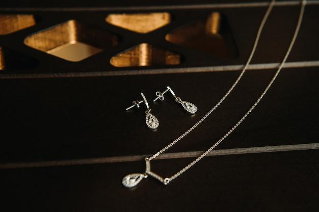 Accessoires pour la mariée. boucles d'oreilles et chaîne avec pendentif. boucles d'oreilles de mariage blanches.