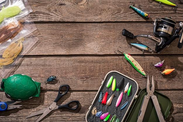Accessoires pour la pêche sur fond de bois. moulinet, fil de pêche, flotteur, hameçons, leurres pour la pêche. vue de dessus. nature morte. espace de copie