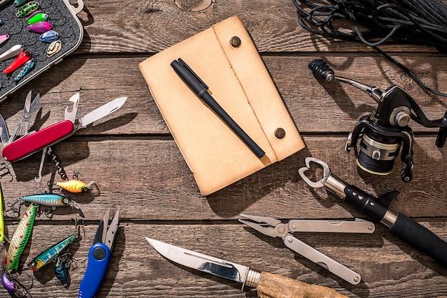 Accessoires pour la pêche sur fond de bois. moulinet, ligne de pêche, flotteur, hameçons, leurres pour la pêche. vue de dessus. nature morte. copier l'espace