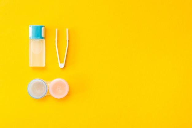 Accessoires pour ranger les lentilles: une bouteille de liquide, un récipient et une pince à épiler
