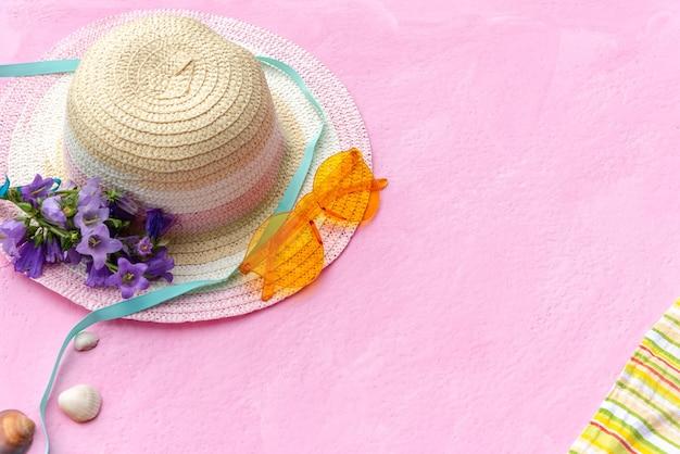 Accessoires pour les vacances d'été avec un chapeau de paille et une couverture avec des lunettes de soleil.
