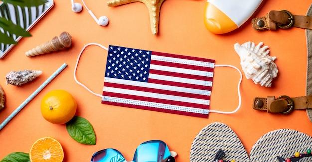 Accessoires pour des vacances à la plage autour d'un masque de protection avec le drapeau des usa
