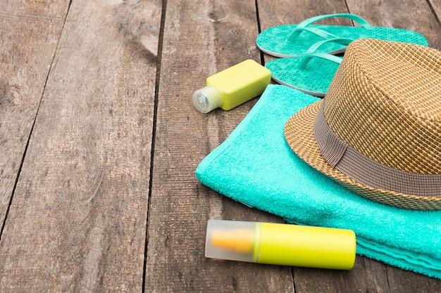 Accessoires pour vacances à la plage comme chapeau de paille, tongs et serviette