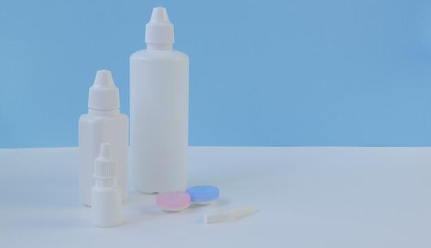 Accessoires et produits pour l'entretien des lentilles de contact sur fond blanc et bleu. composition horizontale. premier plan.