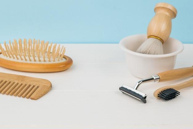 Accessoires de rasage, brosse à dents et peignes sur un tableau blanc sur fond bleu.