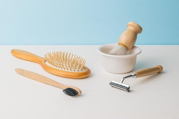 Accessoires de rasage et de lavage en bois élégants sur une table blanche.