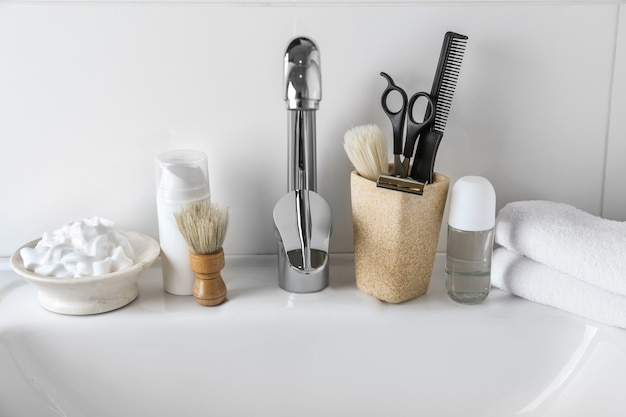 Accessoires de rasage avec des produits cosmétiques pour les hommes sur le lavabo dans la salle de bain