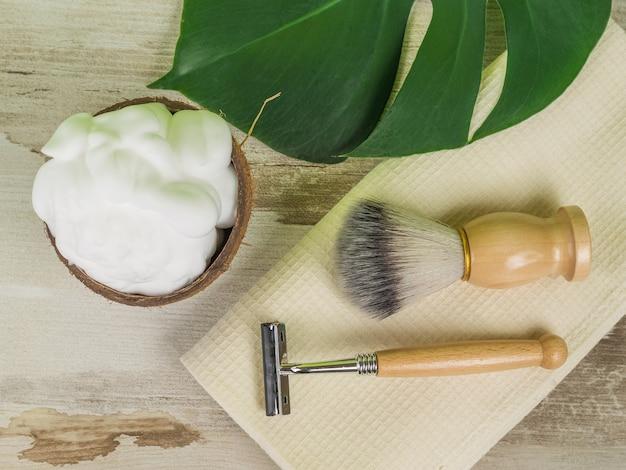 Accessoires de rasage vintage, mousse à raser à la noix de coco et une grande feuille de monstera.
