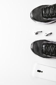 Accessoires de remise en forme sur fond blanc. chaussures de course, serviette, smartphone et casque, vue de dessus.
