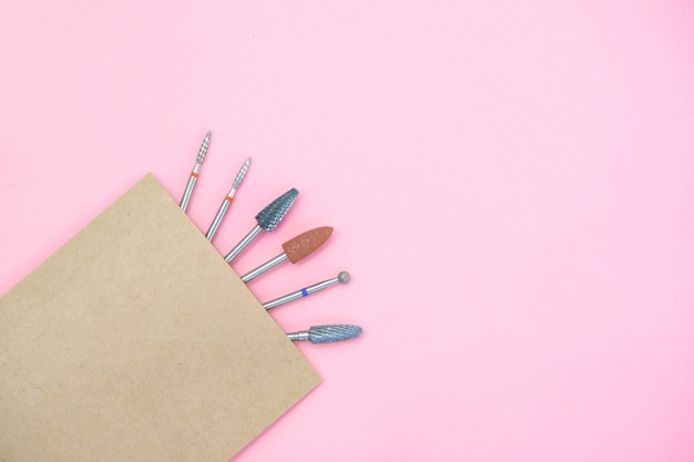 Accessoires remplaçables pour la machine à manucure dans un sac de bricolage après stérilisation. sur fond rose avec espace de copie