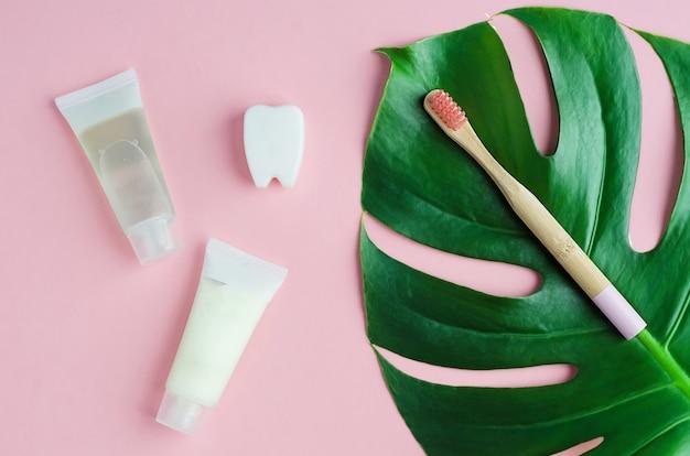 Accessoires de salle de bain, dentifrice à base de plantes bio naturel, brosse à dents en bambou sur feuille de monstera
