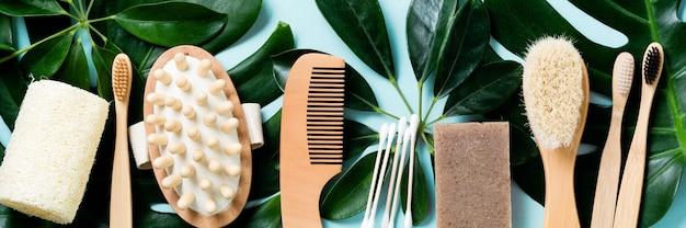 Accessoires de salle de bain écologiques ou outils de spa sur les feuilles de monstera sur une surface bleue.
