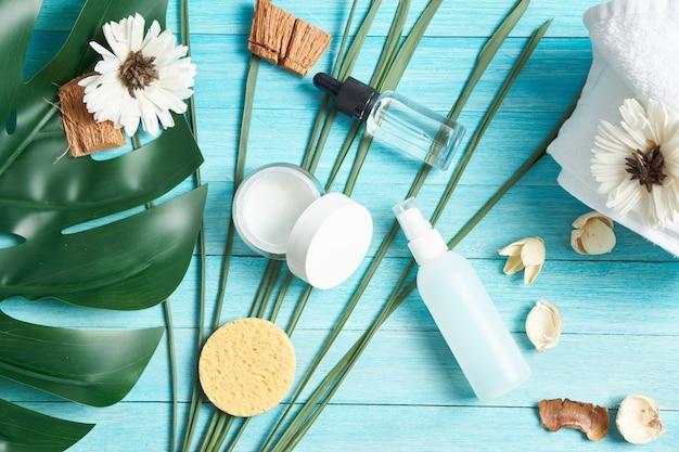 Accessoires de salle de bain savon cosmétique feuilles vertes fond en bois bleu