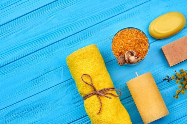 Accessoires de salle de bain spa à plat sur un bureau en bois bleu. sel jaune avec serviette roulée, bougie et savon.