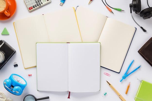 Accessoires scolaires et cahier ou livre avec des pages vides sur fond blanc, vue de dessus