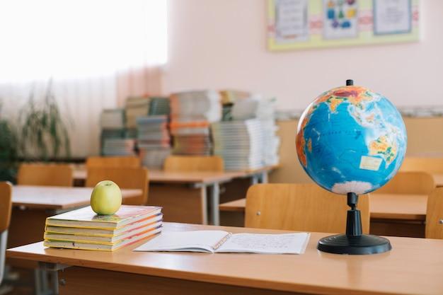 Accessoires scolaires et pomme mis sur le bureau