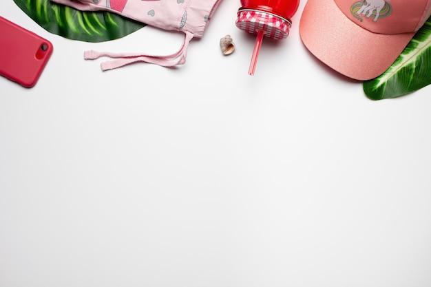 Accessoires et shorts pour filles sur fond blanc avec coquillage et boisson aux feuilles vertes tropicales ...