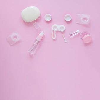Accessoires de soins oculaires sur fond rose avec espace de copie