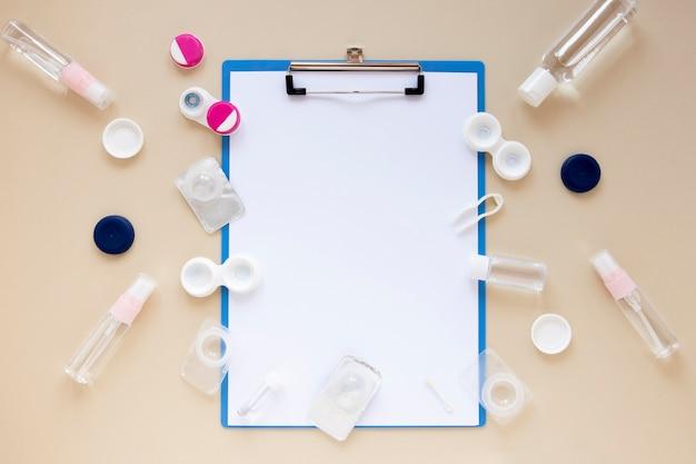 Accessoires de soins oculaires vue de dessus sur fond beige avec la maquette du presse-papiers
