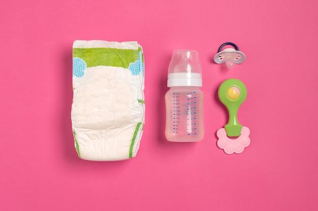 Accessoires de soins pour bébés et couches sur fond rose. vue de dessus. espace de copie. nature morte. mise à plat