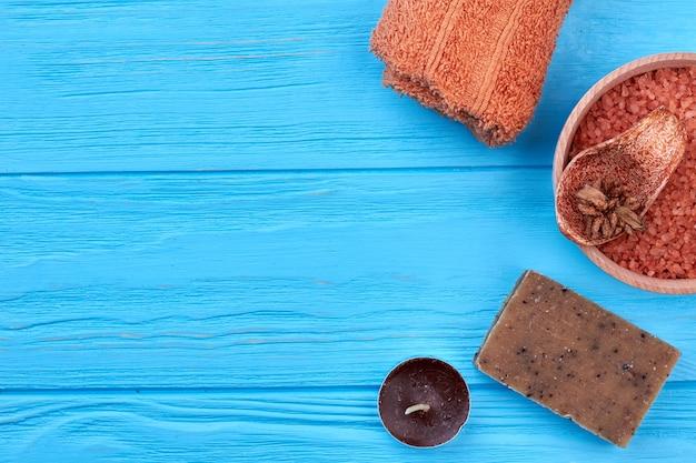 Accessoires de spa de bain sur un bureau en bois bleu et un espace de copie. bougie brune avec savon et serviette.