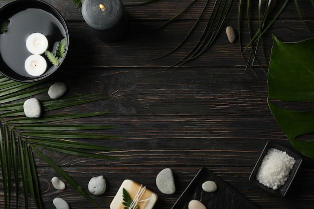 Accessoires de spa et feuilles de palmier sur fond en bois, espace pour le texte