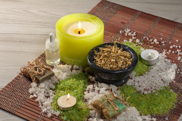 Accessoires de spa avec savon, bol avec fleurs de camomille séchées, bouteilles d'huile aromatique, sel de mer, bougies sur serviette en bambou