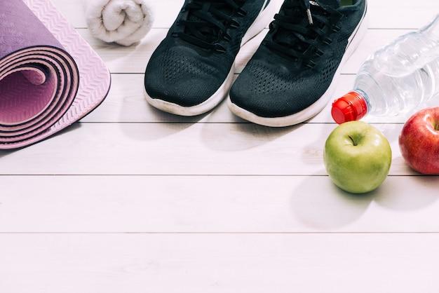 Accessoires de sport pour dames tels que chaussures de sport, haltères, tapis de yoga avec eau et pomme. concept de remise en forme, de sport et de mode de vie sain. vue de dessus, espace de copie