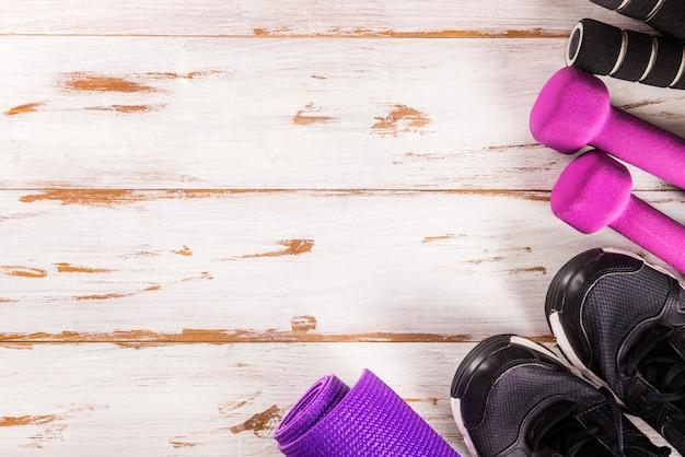Accessoires de sport pour dames, vue de dessus, fond en bois