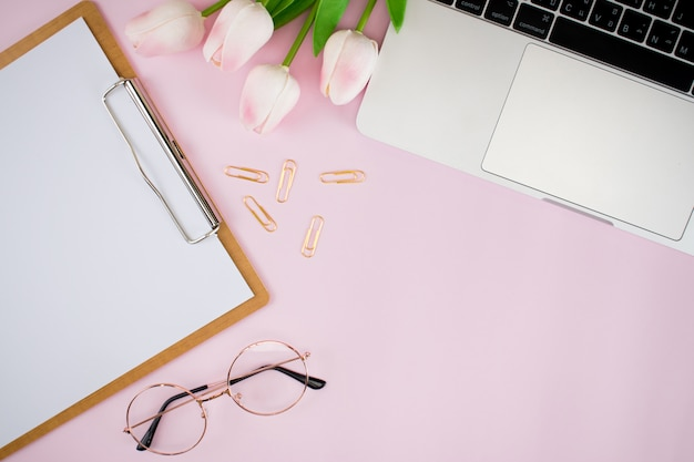 Les accessoires de travail pour femmes reposent à plat sur du papier rose pastel rose. photos prises de la vue de dessus style simple avec espace pour la saisie de texte.