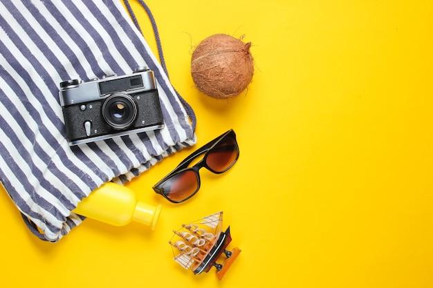 Accessoires de vacances à la plage sur fond jaune. contexte créatif de l'été.