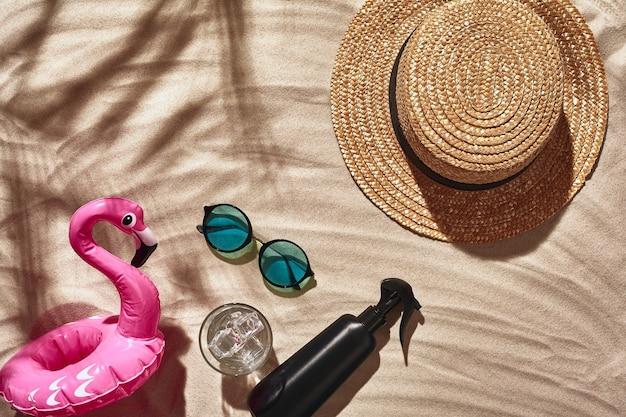 Les accessoires de vacances des voyageurs sont disposés sur une plage de sable blanc vue de dessus à plat