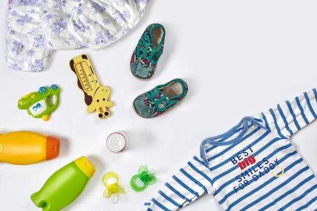 Accessoires et vêtements de soins de bébé sur la vue de dessus de fond blanc