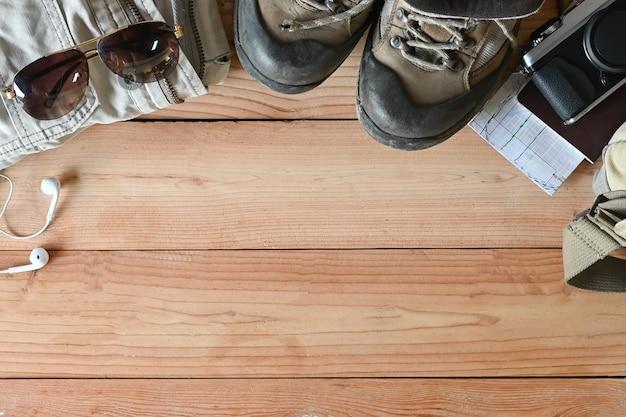 Accessoires de voyage sur bottes de randonnée en bois, veste, sac à dos, carte, appareil photo et lunettes de soleil en bois avec espace de copie.