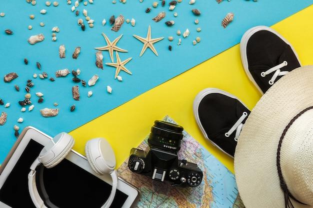Accessoires de voyage caméra, chapeau de paille, carte, chaussures sur une disposition de vue de dessus plat bluebackground jaune avec espace de copie